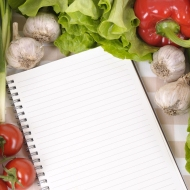 Selection of salad vegetables with lined notebook on a check tablecloth.